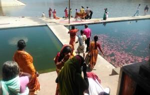 Pushkar, aspetti di un ghat con i petali dei rituali che galleggiano sull'acqua e di donne accanto al tempietto.
