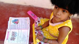 Orissa, Puri, 12 gennaio 2016, pomeriggio. La figlia di una negoziante mentre sta eseguendo i compiti sulla via.