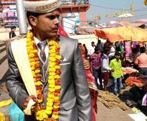 Varanasi, 19 febbraio 2016. Uno sposo arriva al ghat tirando la moglie con la sciarpa annodata al mantello di lei.