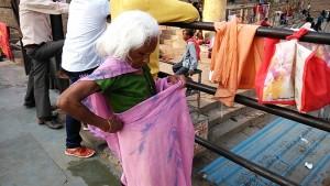Varanasi, 16 febbraio 2017. Anziana che si riveste dopo il bagno nel Ganga river.
