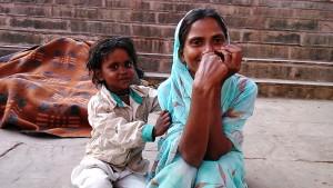 Varanasi, 3 marzo 2017. Madre con bambina accanto alle loro coperte, verso sera, sui ghat.